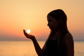 Person standing in front of a blurry sunset above the water. They are in profile and shadowed by the light behind them. Their hand is out, as if they are holding the setting sun in the palm of their hand.