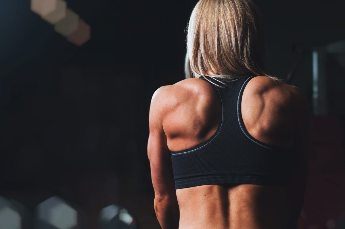 A person in a sports bra faces away. The muscles on their back are very well defined.